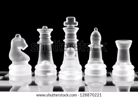 Chess pieces on glass chessboard over black background