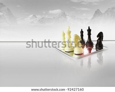 Chess pieces on white reflective foreground with abstract winter mountain scape in background - stock photo