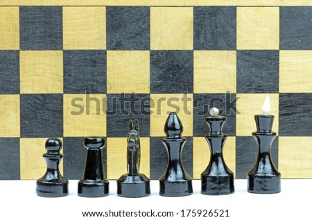 Chess pieces with wood board in background - stock photo