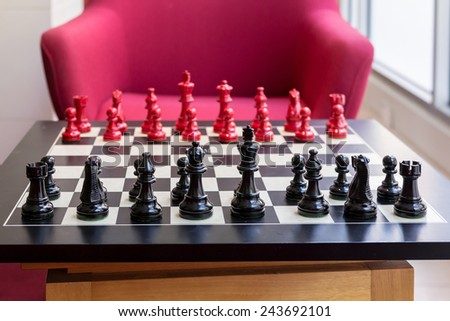 Chess set on a table with red chair background - stock photo