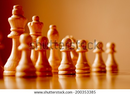 Chess set on a wooden chess board with the pieces lined up on two receding oblique lines with focus to a central pawn in the front row and copyspace, low angle view - stock photo