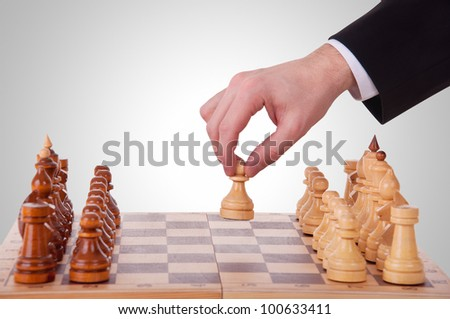 chess. The first step. hand chess and a chess board with chess pieces - stock photo