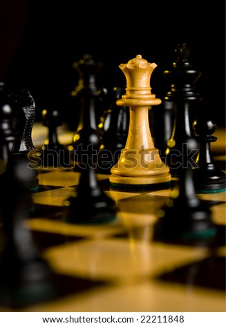 Chess white queen threatened by black pieces which surround her. Lit by firelight. - stock photo