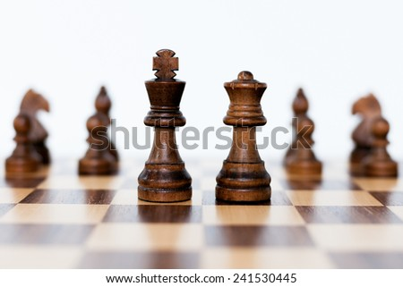 Chess wooden pieces and chess wood board on white background - stock photo