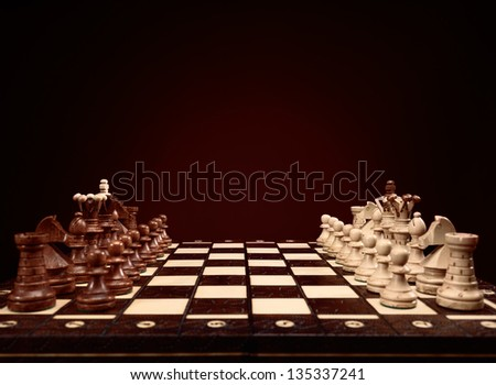 Chessboard with chess pieces, board game on brown background - stock photo