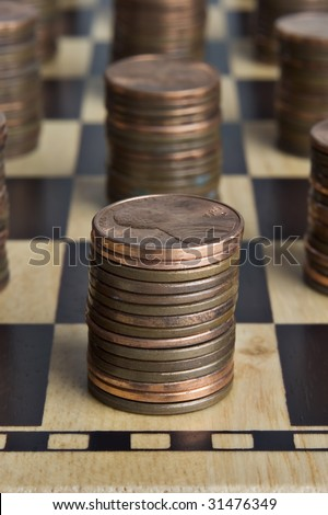 Chessboard with stacks of pennies - stock photo