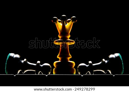 Chessmen on a chess board. A dark background and art illumination.