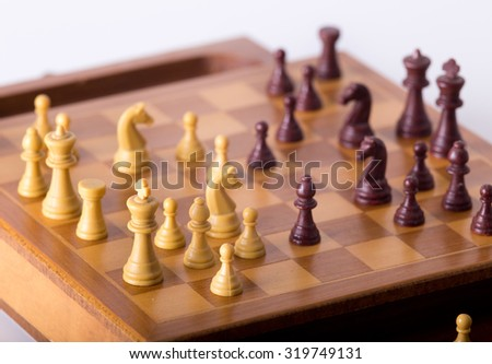 Chessmen on wooden board isolated on white background