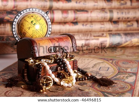 Chest with jewelry, globe on antique map - stock photo