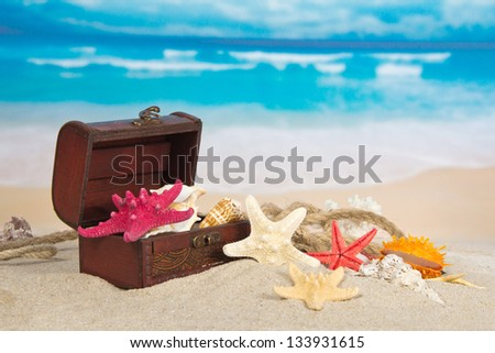 Chest with sea cockleshells and stars on sea sand - stock photo
