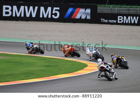 CHESTE, SPAIN- NOVEMBER 6: Several riders of moto2 in a curve participating in the final race of Grand Prix 2011 on November 6, 2011 in Cheste (Valencia), Spain
