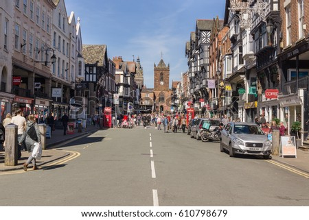Chester England UK - March 25 2017: Shoppers and visitors on Bridge Street with its beautiful half timbered buildings and the church of Saint Peters in the historic city of Chester