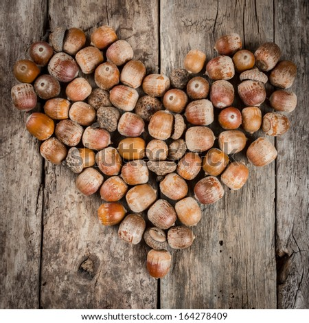 Chestnuts and acorns forming a heart on wooden background - stock photo