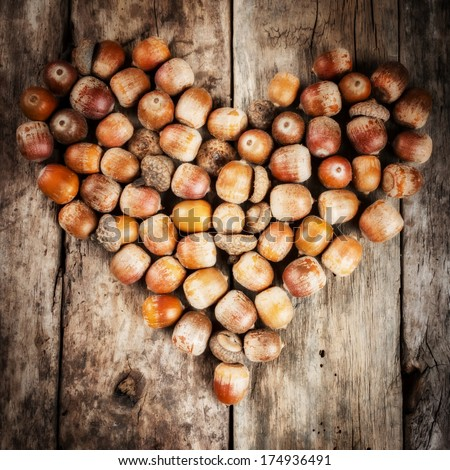 Chestnuts and acorns forming heart on a wooden background - stock photo