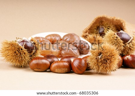 Chestnuts and marron glace over a light brown background