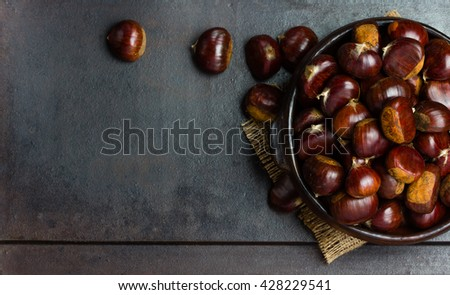 Chestnuts castanas in clay bowl on black background. Top view - stock photo