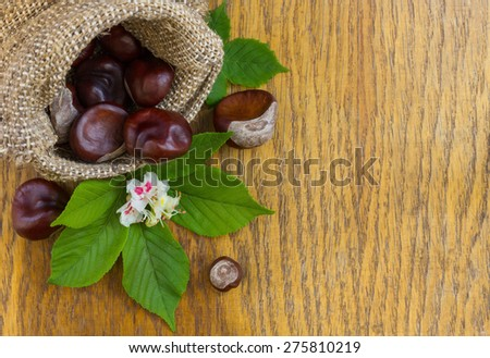 Chestnuts in burlap on wood textured - stock photo