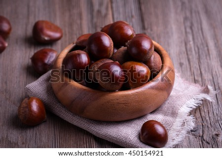 chestnuts on the old wooden table - stock photo
