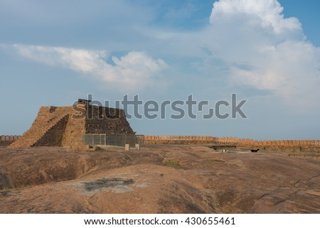 Chettinad, India - October 16, 2013: A pyramid with cannon stands on top of plateau at the Thirumayam fort. The rampart and battlements form a line under blue skies. - stock photo