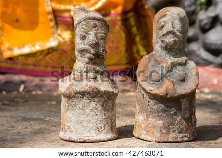 Chettinad, India - October 16, 2013: Ayyanar, village protector, Horse shrine of Namunasamudran. Clay male and female figurines are offered to influence the gender of the child during pregnancy. - stock photo