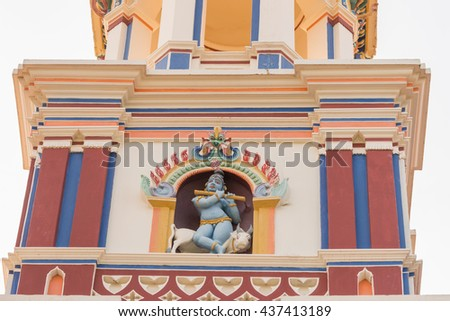 Chettinad, India - October 17, 2013: Chidambara Palace in Kadiapatti. Krishna statue on top of facade. He sits on bull and plays the flute. Niche and towers. - stock photo