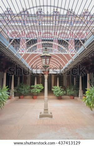 Chettinad, India - October 17, 2013: Chidambara Palace in Kadiapatti. Reception courtyard comes with antique street lantern and illusion of ceiling created with metal fence. Colorful facade shows. - stock photo