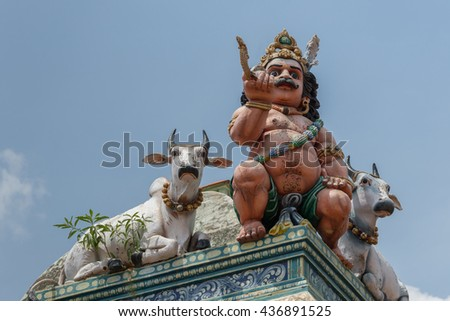 Chettinad, India - October 17, 2013:Detail of the Shiva temple at Kottaiyur shows half-naked Ayyanar on wall in company of two bulls against blue sky. - stock photo