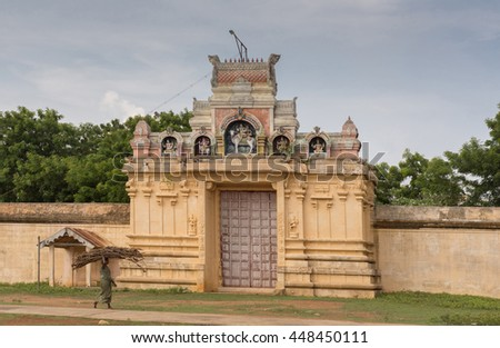 Chettinad, India - October 18, 2013: Entrance to Nagar Soorakudi Sundesaswar Meenakshi Ambal Temple. Yellow wall and decorated gate while woman with firewood on her head goes by. - stock photo