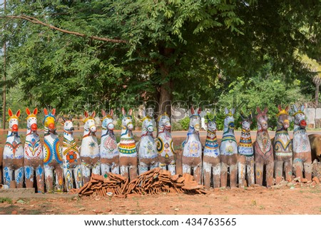 Chettinad, India - October 17, 2013: Kothamangalam Ayyanar horse shrine. Row of laughing white horses, looking at us, with red, green and yellow trim and body paintings. - stock photo