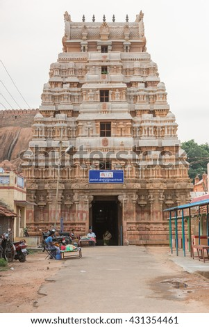 Chettinad, India - October 16, 2013: The gopuram of the Lord Vishnu temple in Thirumayam village. The battlements of the fort in background. A few people at entrance. - stock photo
