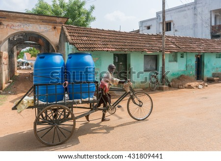Chettinad, India - October 17, 2013: Two large blue vats of drinking water on top of bicycle cart pushed by man in street, - stock photo