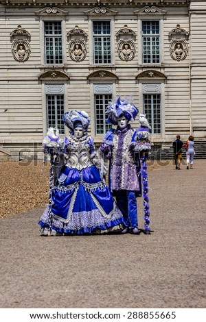 CHEVERNY, FRANCE - JUNE 10, 2015: Venetian carnival (costume party) enthusiasts, dressed in colorful costumes, masks and feathers, have animated the field of Cheverny. - stock photo