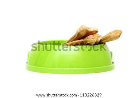 Chewing dog bone in a bowl isolated on a white background - stock photo