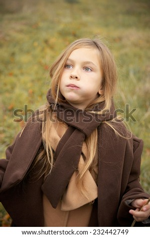Chewing little girl outdoors. - stock photo