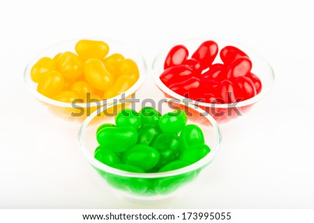 chewy candy jelly beans red, yellow and green colors in the round plates on white background
