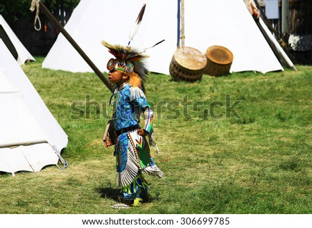 CHEYENNE, WYOMING - July 25, 2015 - Young Native American boy wandering around the tee pees before performing at a pow-wow - stock photo