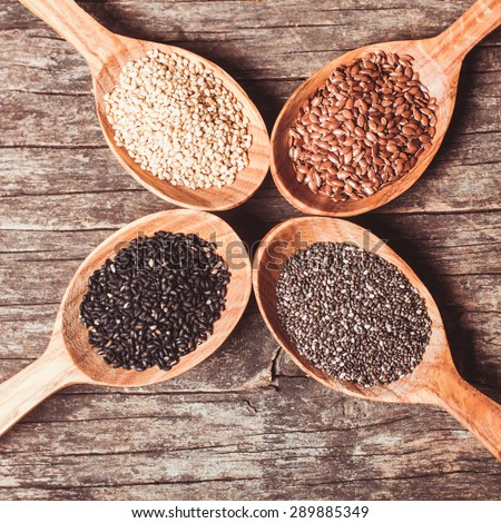Chia and flax seeds, white and black sesame in wooden spoons - stock photo
