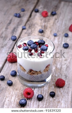 Chia breakfast cereal with yogourt and berries, on wooden background - stock photo