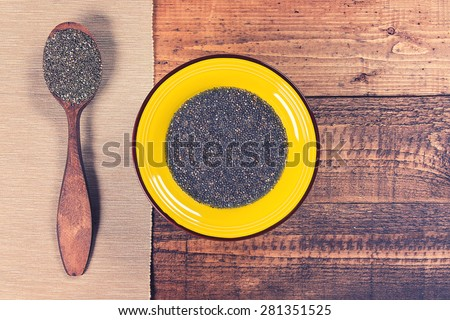 Chia jelly in a plate with spoon full of dry chia seeds on grunge wooden background. Toned. - stock photo