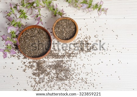 Chia seed healthy super food with flower over white wood background. Salvia hispanica. - stock photo