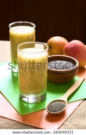 Chia seed (lat. Salvia hispanica) and mango juice photographed with natural light. Chia seeds are considered a superfood (Selective Focus, Focus on the front of the juice and the seeds on the spoon) - stock photo