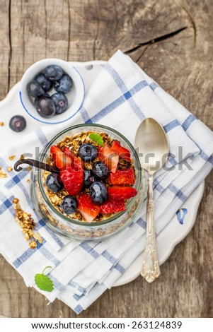 Chia Seed Pudding and caramel oat flakes, blueberries and strawberries in a transparent glass on a wooden background. Selective focus. Concept of healthy food - stock photo
