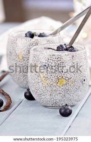 Chia seed pudding made with mangoes and blueberries with extreme shallow depth of field. - stock photo