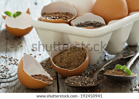 Chia seeds and flaxseed - egg replacers placed in egg shells - stock photo