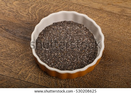 Chia seeds heap in the bowl over wood background