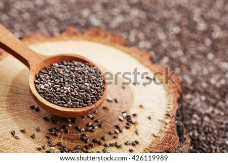 Chia seeds in wooden spoon, lying on dark stone background.