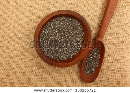Chia Seeds Inside Wooden Bowl And Spoon On Burlap Bag - stock photo