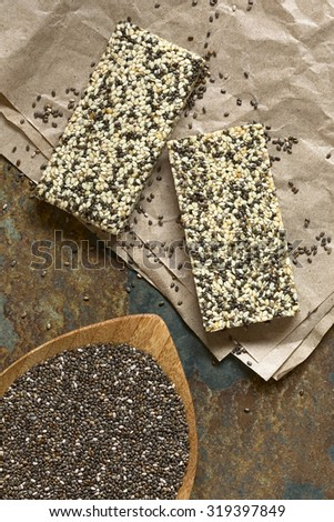 Chia seeds (lat. Salvia hispanica) and chia-sesame-honey granola bar, photographed overhead with natural light. Chia is considered a superfood containing protein, omega fat, minerals, antioxidants. - stock photo