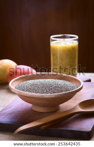 Chia seeds (lat. Salvia hispanica) in bowl photographed with natural light. Chia seeds are a superfood containing protein, omega fat and antioxidants. (Selective Focus, Focus one third into the bowl) - stock photo
