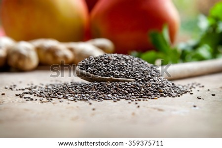 Chia seeds on a wooden spoon with apples, ginger and greens in the background - stock photo